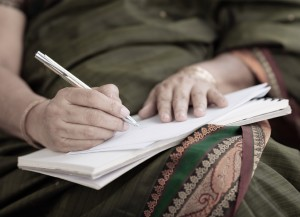 Hands of Indian woman writing a letter